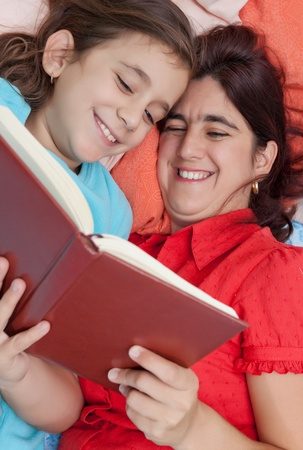 Latin mother and daughter laying in bed and reading a book photo