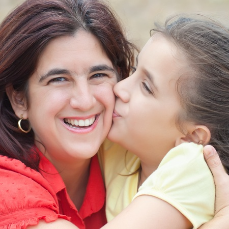 Square portrait of a cute latin girl kissing her beautiful mother with a diffused grass background Stock Photo - 10453455