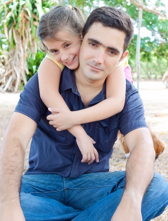 Adorable latin girl hugging her father on the park Stock Photo - 10444628