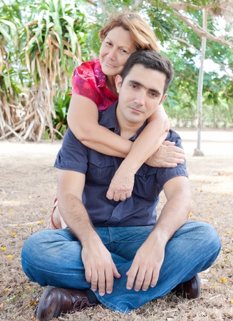 Mature latin woman hugging a young man on a beautiful park Stock Photo - 10444631