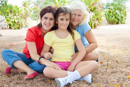 Three generations of latin women hugging and sitting in a park Stock Photo - 10444633