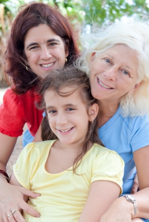 Three generations of latin women hugging and sitting in a park Stock Photo - 10444647