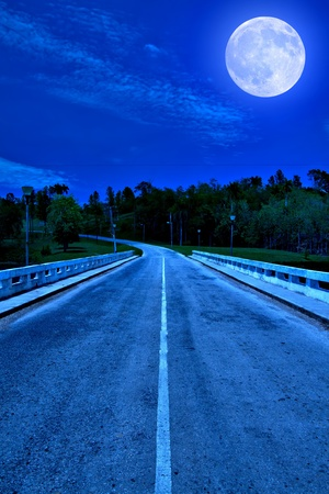 dream land: Lonely road surrounded by the forest illuminated by a bright full moon at midnight