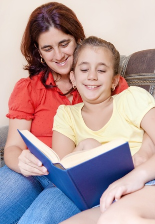 Latin mother and daughter reading a book together photo
