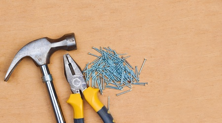 space wood: Hamer, pliers and nails over a wood panel