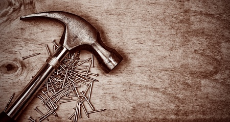 iron nail: Hammer and nails over a wood panel with space for text in dark sepia shades