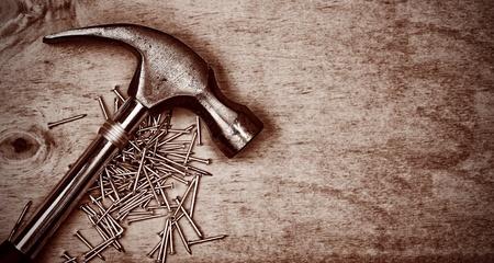herramientas de carpinteria: Martillo y clavos en un panel de madera con espacio para texto en negro tonos sepia Foto de archivo