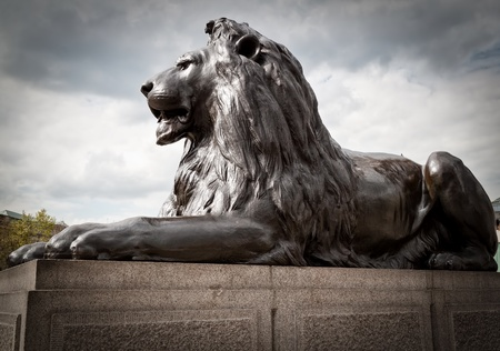 Bronze sculpture of a lion in Trafalgar Square, London on a typical british cloudy day photo