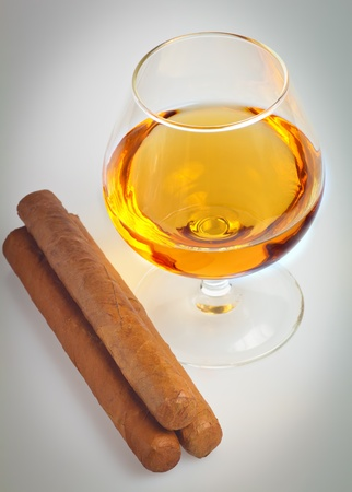 Glass of cognac with cuban cigars photo