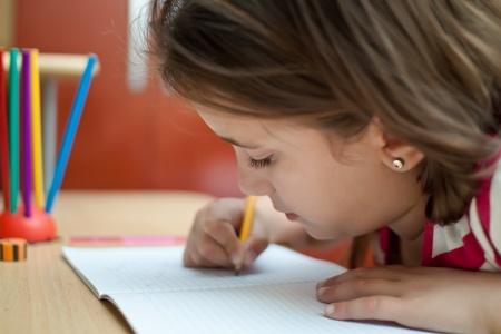 Small latin girl working on her homework photo