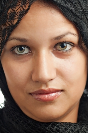 Portrait of a young girl with beautiful green eyes dressed as an arab woman isolated on a white background photo