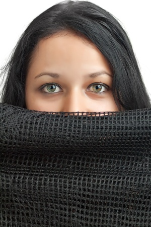 Beautiful latin or arabic girl with gorgeous green eyes hiding behind a black cloth isolated on a white background