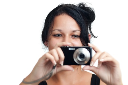Young latin girl taking a picture with a compact camera isolated on a white background photo