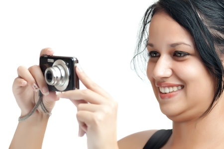Beautiful latin girl taking a picture with a compact camera isolated on a white background photo