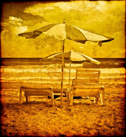 old fashioned sepia: Vinatage postcard with umbrellas on a beach