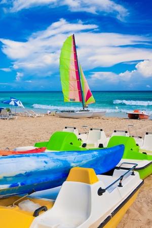 Colorful kayaks, water bikes and catamaran on the cuban beach of Varadero photo