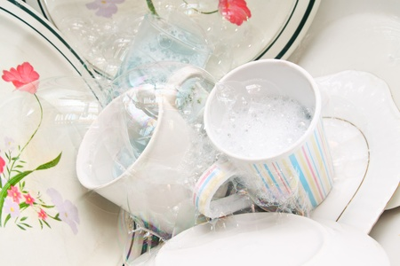 wash dishes: Washing dirty glasses and dishes with detergent and water Stock Photo