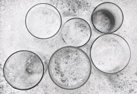 lavar platos: Lavado de vasos sucios con agua y detergente