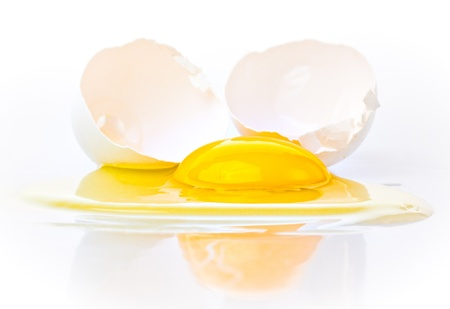 egg white: Broken egg on a white background with a bright yellow yolk Stock Photo
