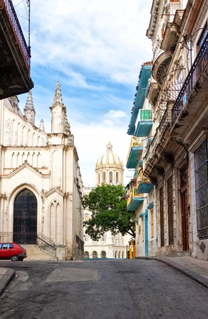 Street in Old Havana sidelined by a church and old typical buildings photo