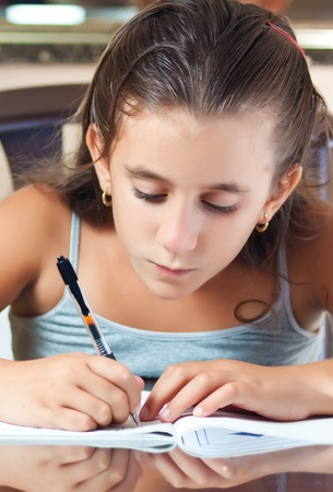 Young latin girl working on her homework Stock Photo - 11116460