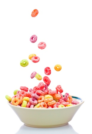 cereal bowl: Colorful childrens cereal falling into a bowl Stock Photo