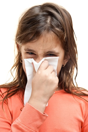 Girl sneezing on a paper tissue isolated on white photo