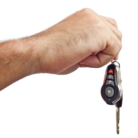 purchasing: Hand giving out new car keys isolated on a white background Stock Photo