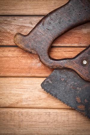 serrucho: Antiguo serrucho de mano sobre un fondo de tableros de madera con espacio para el texto Foto de archivo