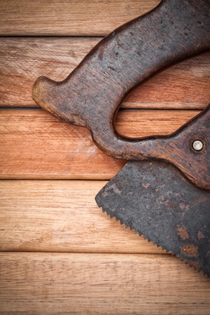 Old handsaw over a wooden boards background with space for text photo