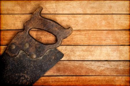 serrucho: Antiguo serrucho sobre un fondo de tablas de madera con espacio para el texto