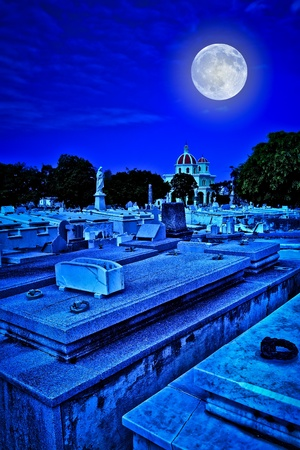 Scary old cemetery at night with a bright full moon shining over the graves photo