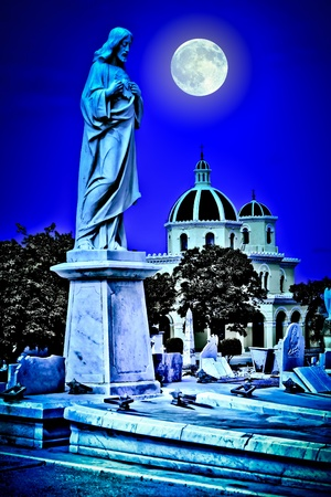 Scary old cemetery at night with a bright full moon shining over the graves and a statue of Jesus in the foreground photo