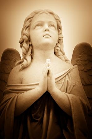 ange gardien: Belle image de cru d'un ange priant dans les tons sépia