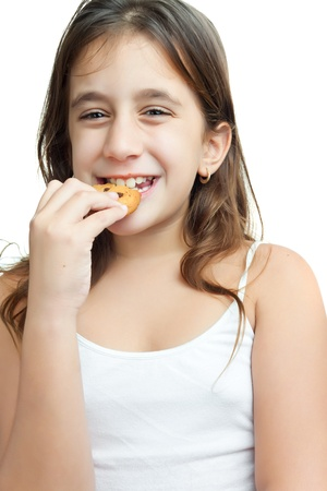 chocolate biscuit: Beautiful latin girl eating a chocolate chips cookie isolated on white Stock Photo