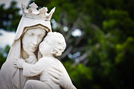 christianism: Marble statue of the virgin Mary carrying a baby Jesus with a diffused vegetation background