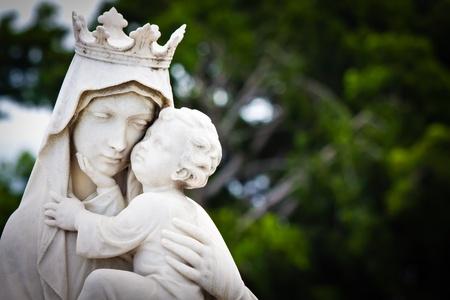 vierge marie: Statue de marbre de la vierge Marie portant un enfant Jésus avec un fond de végétation diffuse Banque d'images