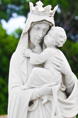 vierge marie: Statue de la vierge Marie portant l'enfant Jésus avec un fond de végétation diffuse Banque d'images