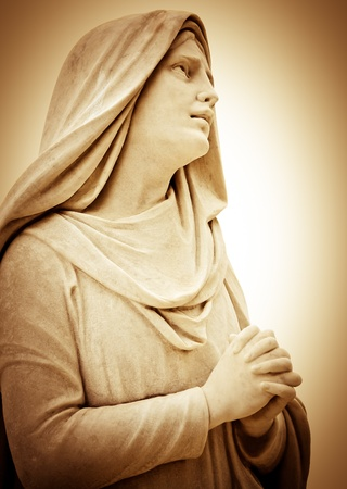 Vintage sepia image of a suffering religious woman praying photo