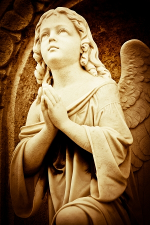 Beautiful vintage image of a praying angel in sepia shades