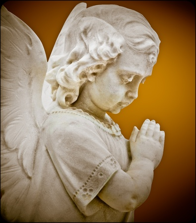 Child angel statue praying with a vintage look photo
