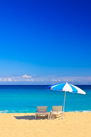 Vertical image of chairs and parasol on the beautiful cuban beach of Varadero with space for text