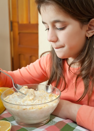 Cute latin girl eating cereal and milk for breakfast photo