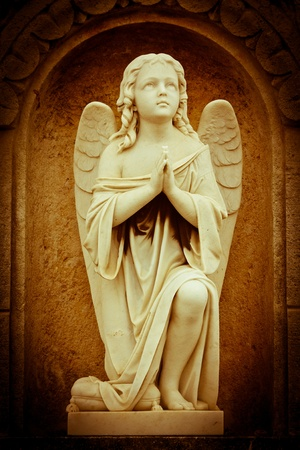 angel cemetery: Beautiful vintage image of a praying angel in sepia shades