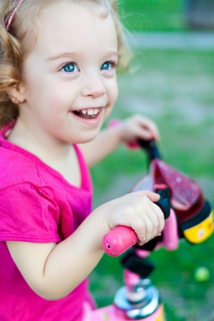 tricycle: Beautiful small girl wearing colorful clothes laughing and riding her bicycle in the park