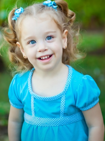 rubia ojos azules: Hermosa niña pequeña con hermosos ojos azules y pelo rubio rizado en un parque