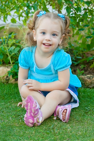 Small blonde girl with gorgeous blue eyes sitting on a park photo