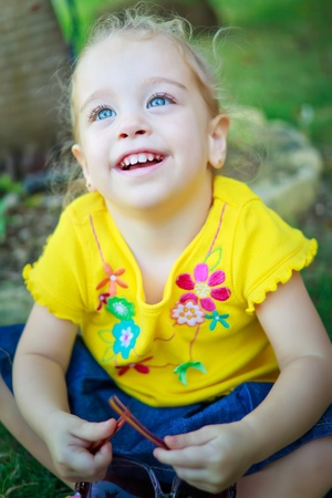 Beautiful small girl with gorgeous blue eyes and blonde curly hair sitting on a park Stock Photo - 12156428