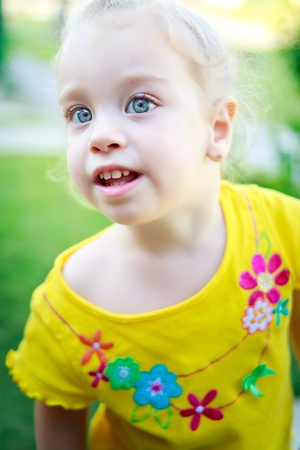 Beautiful small girl with gorgeous blue eyes and blonde curly hair on a park with a shallow depth of field photo