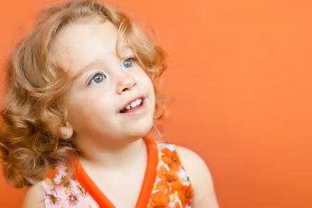 テキスト用のスペースを持つ明るいオレンジ色の背景に笑顔金髪の巻き毛を持つ美しい小さな女の子